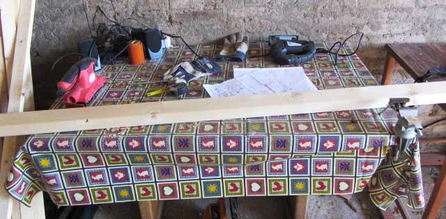 Piano di lavoro: guanti, listelli, seghetto alternativo, levigatore, viti, avvitatore, stereo